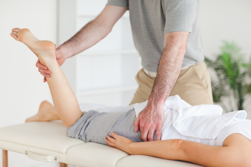 Chiropractor stretches a female customer's leg